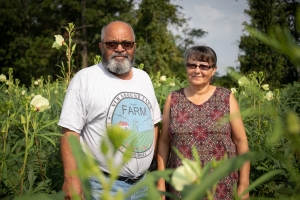 Owners of the New Ground Farm standing in a field of okra.